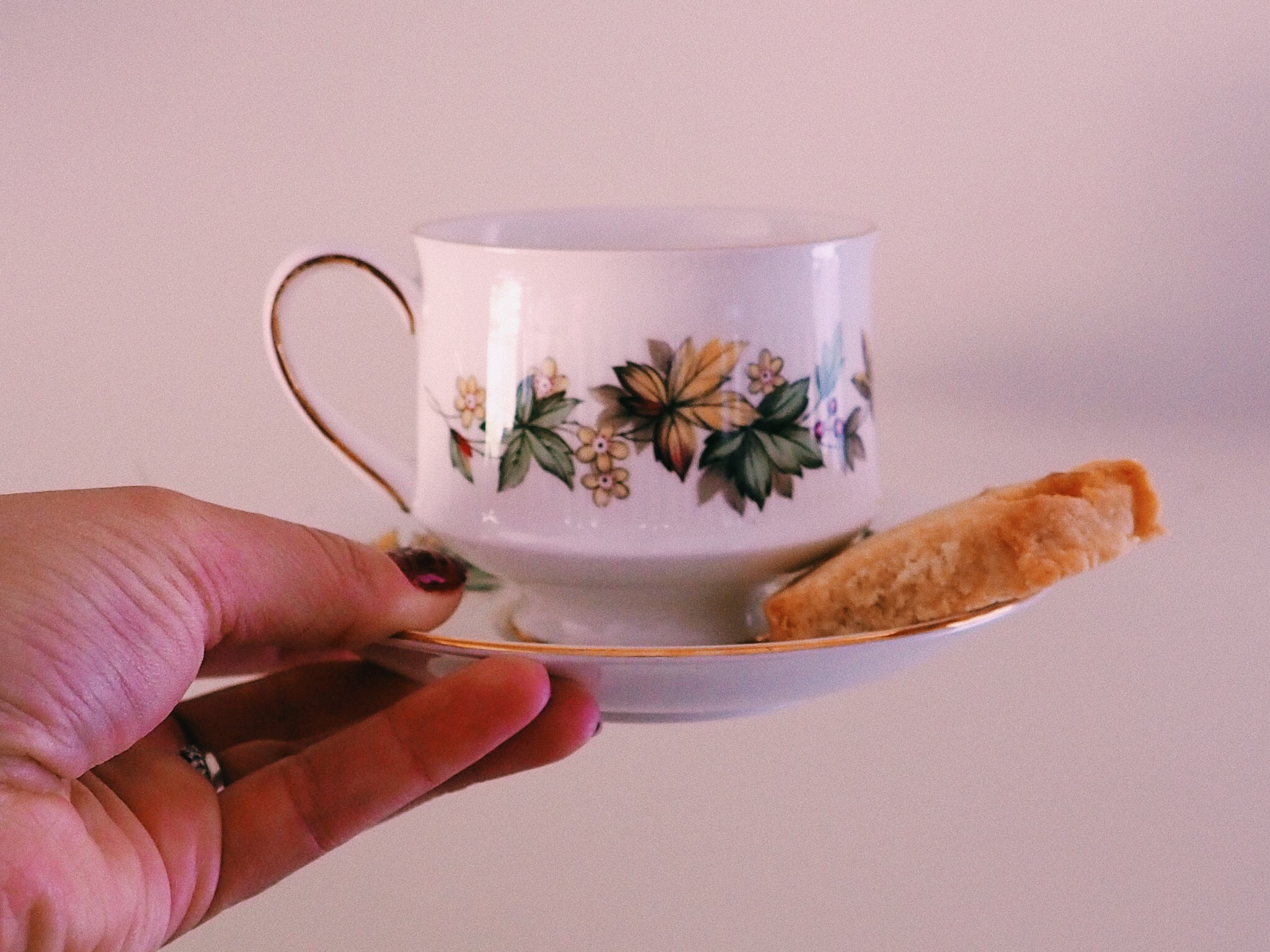 Holding a cup and saucer of tea with a biscuit on the side