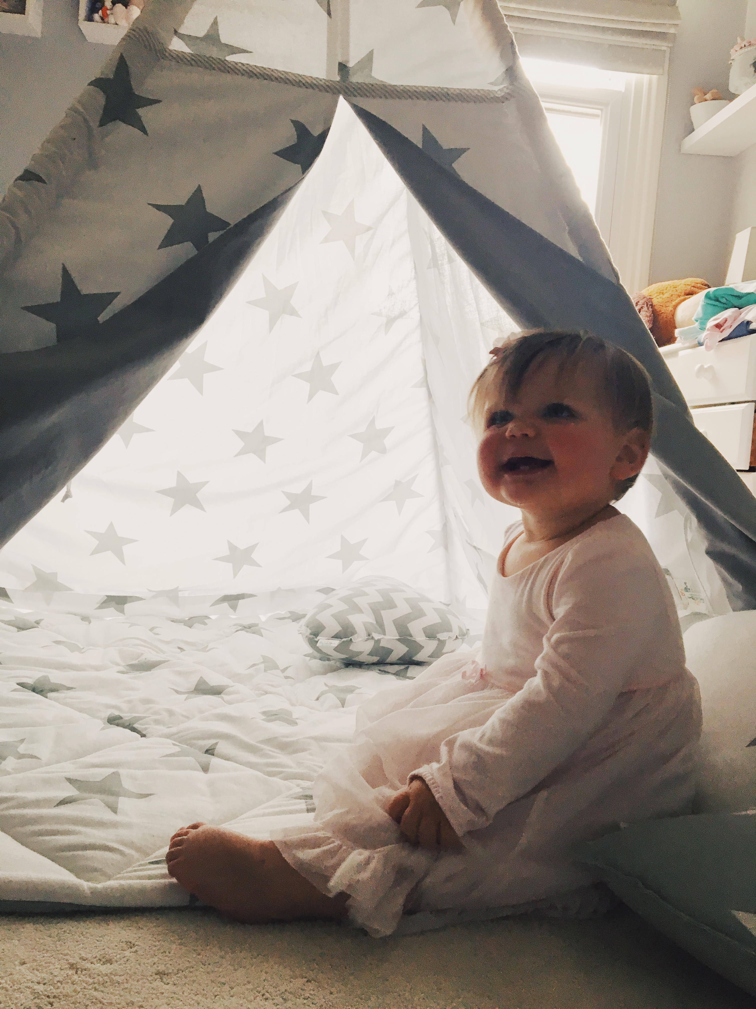 Baby girl playing in her grey and white star tepe in her nursery