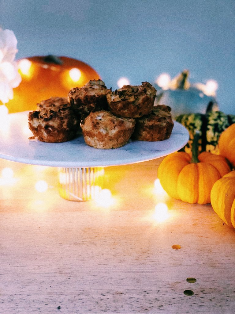 Pumpkin and Parmesan Savoury Muffins on a cake stand surrounded by fairy lights and pumpkins
