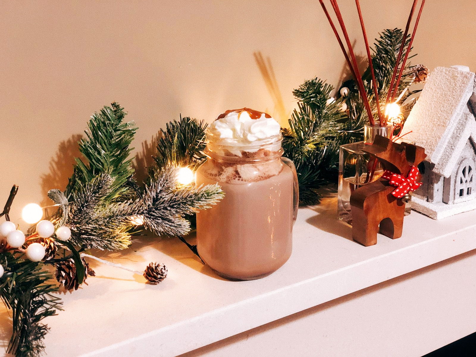 Hot chocolate with whipped cream on a decorated mantle piece