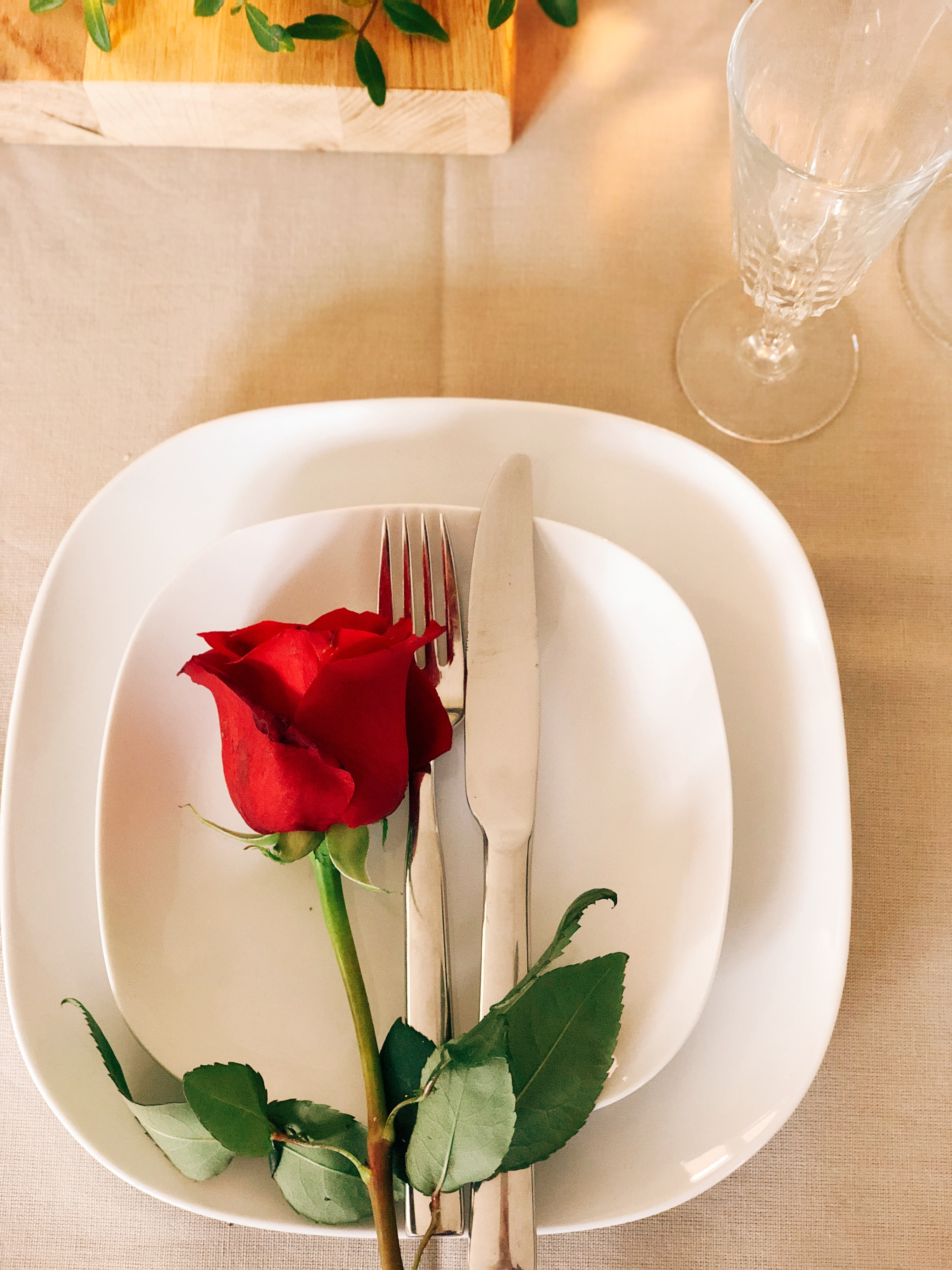 plates cutlery and a single red rose