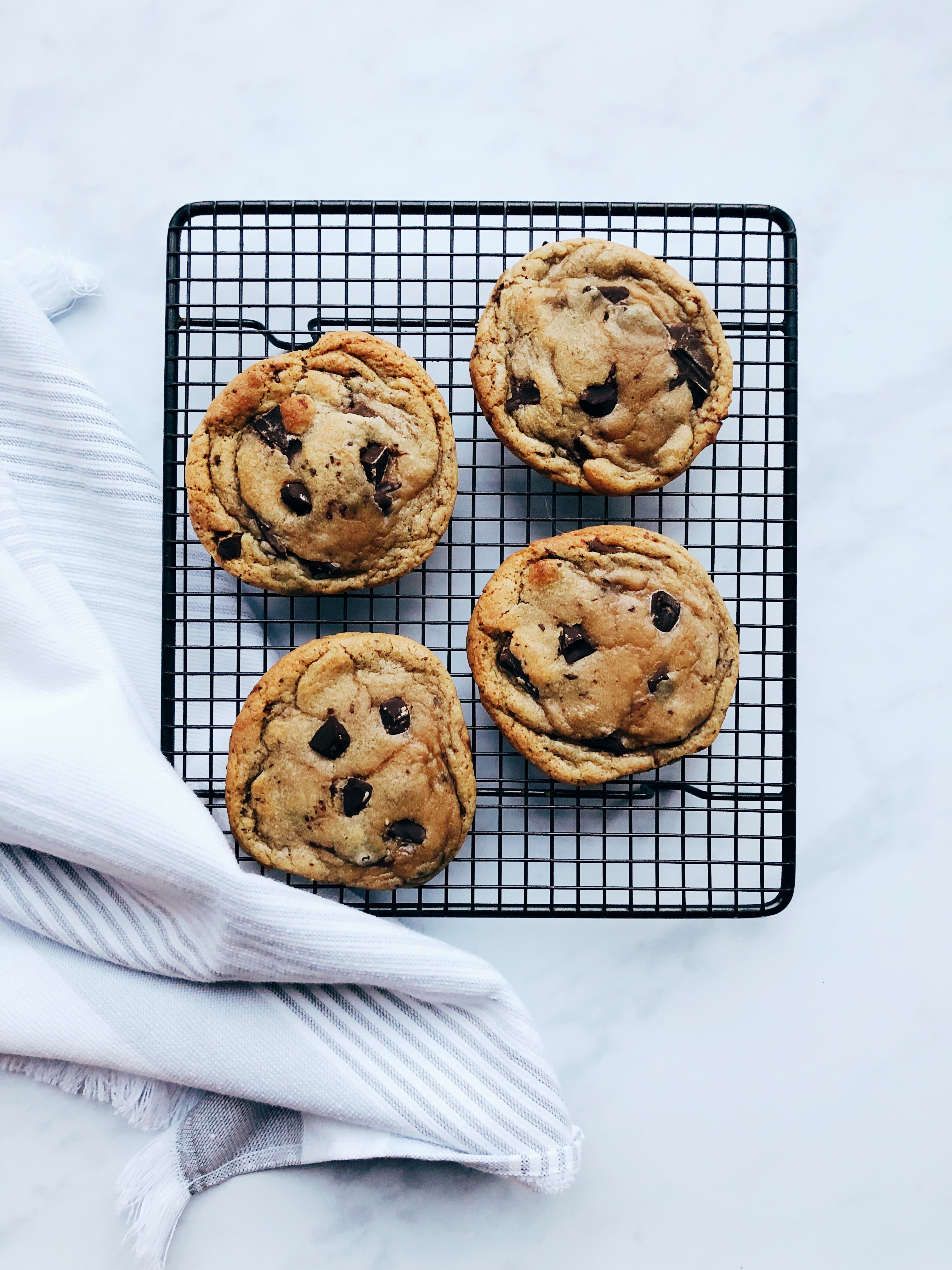 Cookies on a wire cooling rack with teatowel